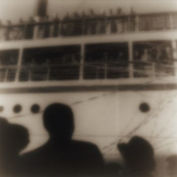 Silhouetted figures at port watching passengers on cruise ship depart.