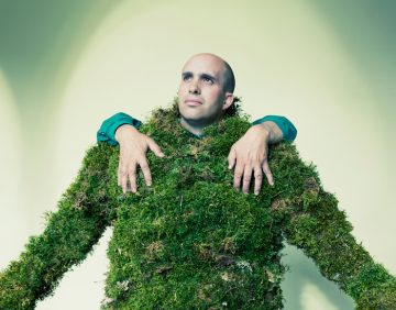 Man dressed in moss with hands on his shoulders.  The Moss Men of Bejar.