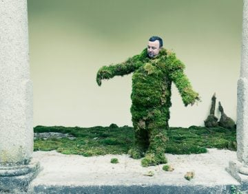 Man trying to walk in a suit of moss.  The Moss Men of Bejar.