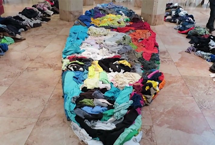 A Giant Anamorphic Portrait Created From Arranged Clothing