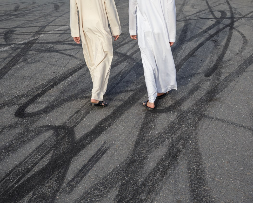 Two men cross a street marked by drifters' tires.