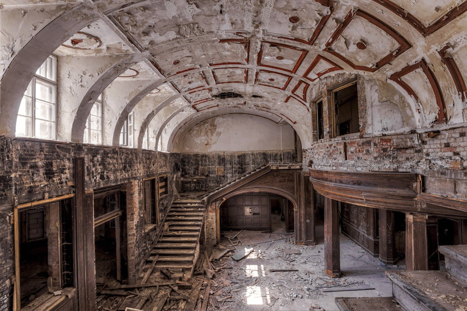 abandoned wooden entry hall with staircase