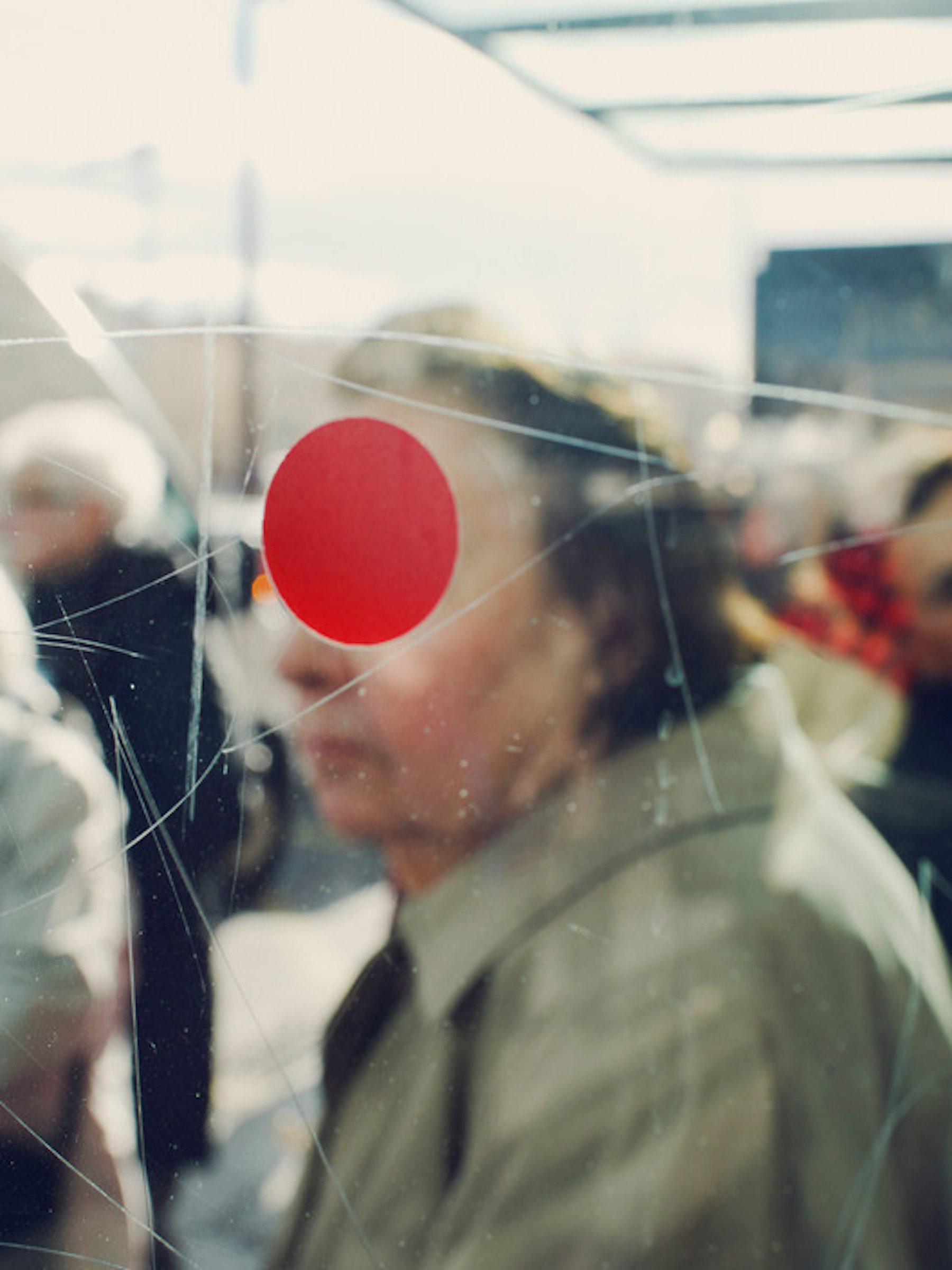 FRANCE. Sete. 2012. A red dot on the glass of a bus stop.