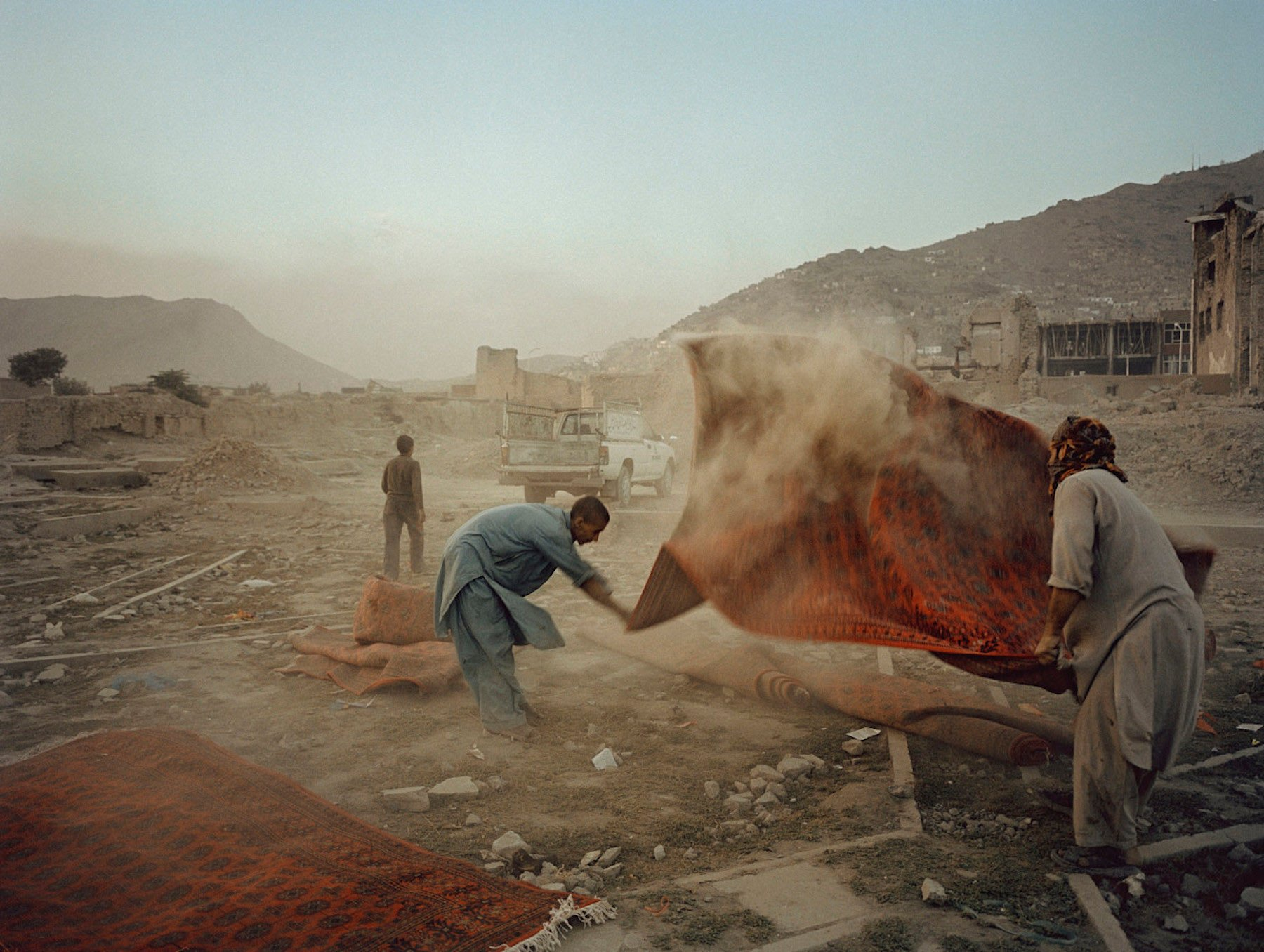 AFGHANISTAN. Kabul. 2004. Men shake dust from rugs that were used for a wedding party.