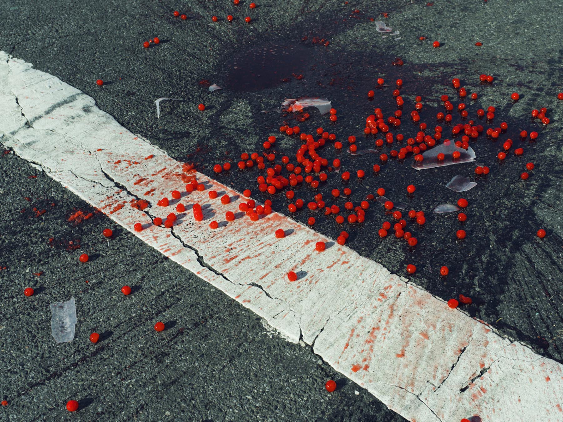 USA. New York City, NY. 2014. Cherries spilled on crosswalk.