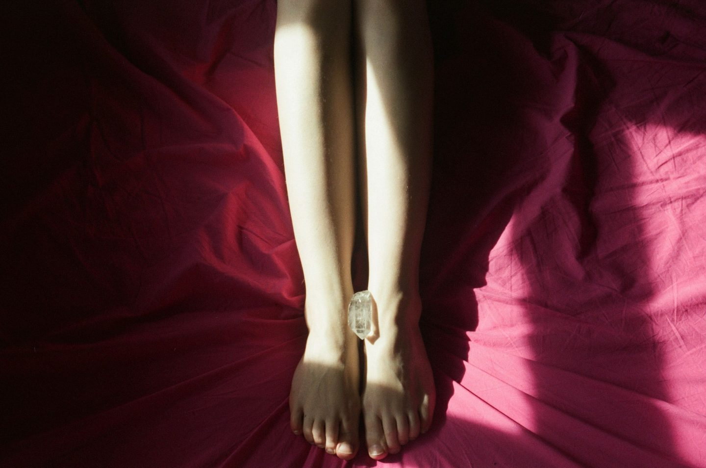 """alt=""""a photoof a piece of crystal is placed between a woman's feet who is in bed on red bedsheets from Lina Scheynius photo - essay for Tabayer jewelry """""""