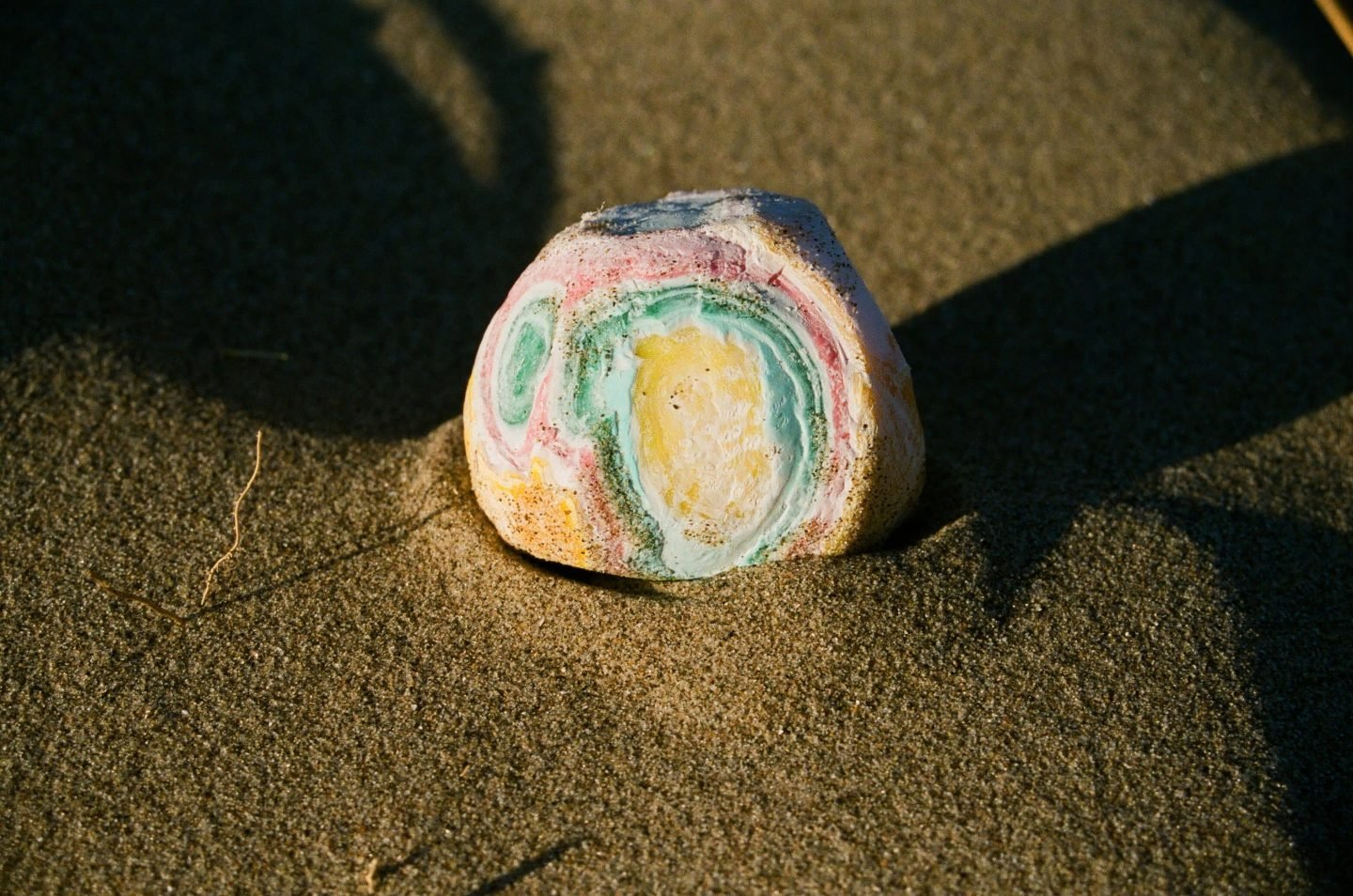 a photo of a colourful stone on the sand from Lina Scheynius photo - essay for Tabayer jewelry